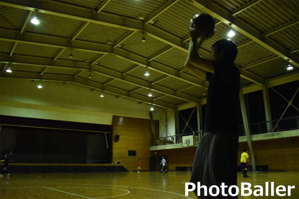 体育館でシュートを打つ青年を横から撮影